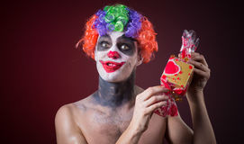 Scary clown with spooky makeup and more candy Stock Photos