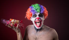 Scary clown with spooky makeup and more candy Royalty Free Stock Photography
