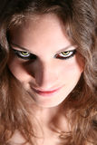 Scary creature. Dangerous looking woman with fierce yellow eyes royalty free stock image
