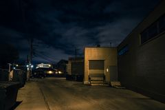 Scary dark city Chicago alley at night. Scary dark city Chicago alley next to an urban warehouse loading dock at night Stock Images