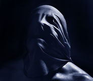 Scary dark portrait. Portrait of a man with a cloth being pulled over the face to create creepy scary torture effect and suffocation Royalty Free Stock Photography