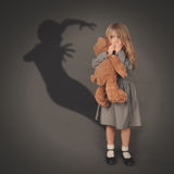Scary Dark Silhouette Ghost Behind Little Child. A little girl is holding a teddy bear and looking at a scary dark silhouette of an evil ghost popping out on a royalty free stock photo