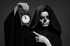 Scary Death Hold A Watch In His Hand. Royalty Free Stock Photos