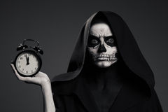Scary Death Hold A Watch In His Hand. Stock Photos