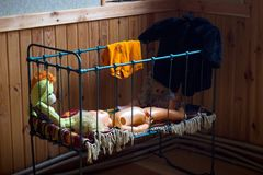 Scary doll in a metal crib Royalty Free Stock Photos
