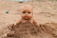 Scary doll in the sand stock photos