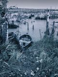 Scary empty uninhabited swamp with old abandoned boats. Monochrome natural background for terrible mystical ideas. Scary empty uninhabited swamp with old royalty free stock images