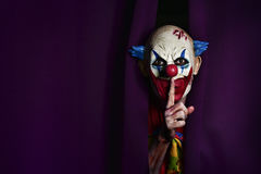 Scary evil clown asking for silence. A scary evil clown peering out from a purple stage curtain, with his forefinger in front of his lips, asking for silence