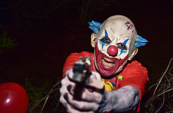 Scary evil clown with a gun Stock Photography