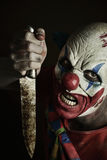 Scary evil clown with a knife. A scary evil clown with a big knife in his hand, against a dark background