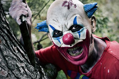 Scary evil clown with a knife. A scary evil clown with a big knife in his hand in the woods Stock Photos