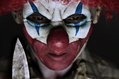 Scary evil clown with a knife. Closeup of a scary evil clown wearing a ragged shirt, holding a big knife next to his face Stock Photo