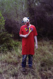 Scary evil clown with a knife in the woods Stock Photo