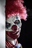 Scary evil clown. Portrait of a scary evil clown against a dark background Stock Images