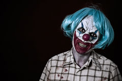 Scary evil clown. Portrait of a scary evil clown wearing a ragged and dirty shirt with blood stains and a blue wig, against a dark background
