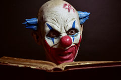 Scary evil clown reading a book Royalty Free Stock Photo