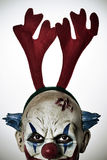 Scary evil clown with reindeer antlers headband Royalty Free Stock Image