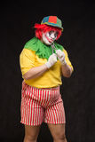 Scary evil clown with an ugly smile and a pair of pliers on a bl Royalty Free Stock Images