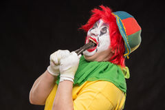 Scary evil clown with an ugly smile and a pair of pliers on a bl Stock Image