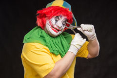 Scary evil clown with an ugly smile and a pair of pliers on a bl Royalty Free Stock Photo
