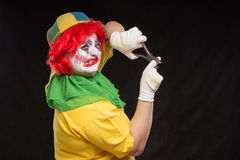 Scary evil clown with an ugly smile and a pair of pliers on a bl Royalty Free Stock Photography