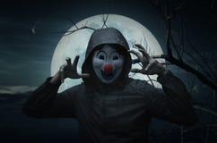 Scary evil clown wear jacket over bird, dead tree, moon and spoo. Ky cloudy sky, Halloween concept royalty free stock photos