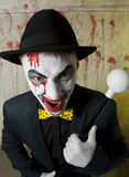 Scary evil clown wearing a bowler hat on wall Stock Photography