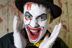 Scary evil clown wearing a bowler hat on wall Stock Photos