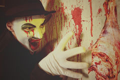 Scary evil clown wearing a bowler hat Stock Photos