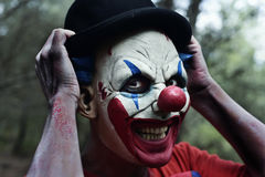 Scary evil clown in the woods Stock Images