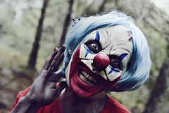 Scary evil clown in the woods. Closeup of a scary evil clown in the woods touching his blue hair and smiling Royalty Free Stock Image