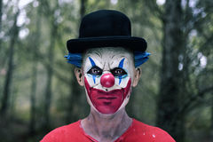 Scary evil clown in the woods. Closeup of a scary evil clown wearing a bowler hat in the woods
