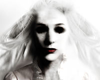 Scary Evil Ghost Woman in White. A scary evil woman with black eyes and red lips is death on a white background for a fear or Halloween concept royalty free stock image