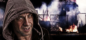 Scary evil man with hood on a background of street riots. Royalty Free Stock Images