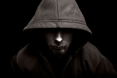 Scary evil man with hood in the dark. Scary evil man with hood in darkness Royalty Free Stock Image