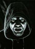 Scary evil man. With hood in darkness Stock Images