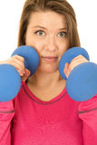 Scary expression of a young woman holding blue barbells Stock Image