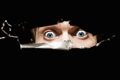 Scary eyes of a man spying through a hole. In the wall closeup Royalty Free Stock Photography