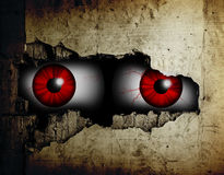 Scary eyes. Scary eyes of a man spying through a hole in the wall Royalty Free Stock Image