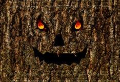Scary face burning eyes, halloween background lantern jack on bark Stock Image