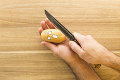 Scary face potato being cut on a wooden kitchen board Royalty Free Stock Photography