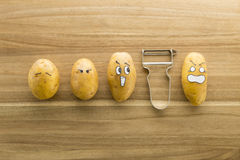 Scary face potatoes and peeler on wooden cutting board Royalty Free Stock Photography