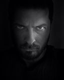 Scary face in the shadow. Low-key portrait of scary looking man Royalty Free Stock Photo