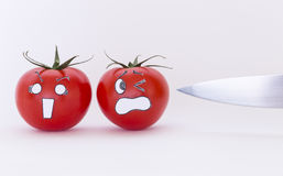 Scary face tomatoes and sharp knife Royalty Free Stock Photos