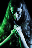 Scary face of a young woman in green and grey lights Stock Photography