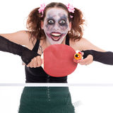 Scary female clown is playing ping-pong Stock Photo
