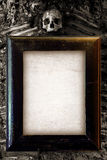 Scary Frame. Old wooden frame and blank paper hanged on a wall with skull on top Royalty Free Stock Image