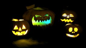 Scary funny angry big orange halloween pumpkins in fire, fog, dark, mist, dusk. Pumpkin exhales smoke, breathes color. Steam stock video