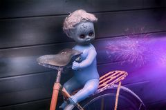 Scary ghost plastic doll with black tears at bicycle on mystic night nature background. Photo royalty free stock photography