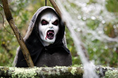 Scary Ghoule. Decorative hooded Ghoul with bloodied mouth and fangs royalty free stock images